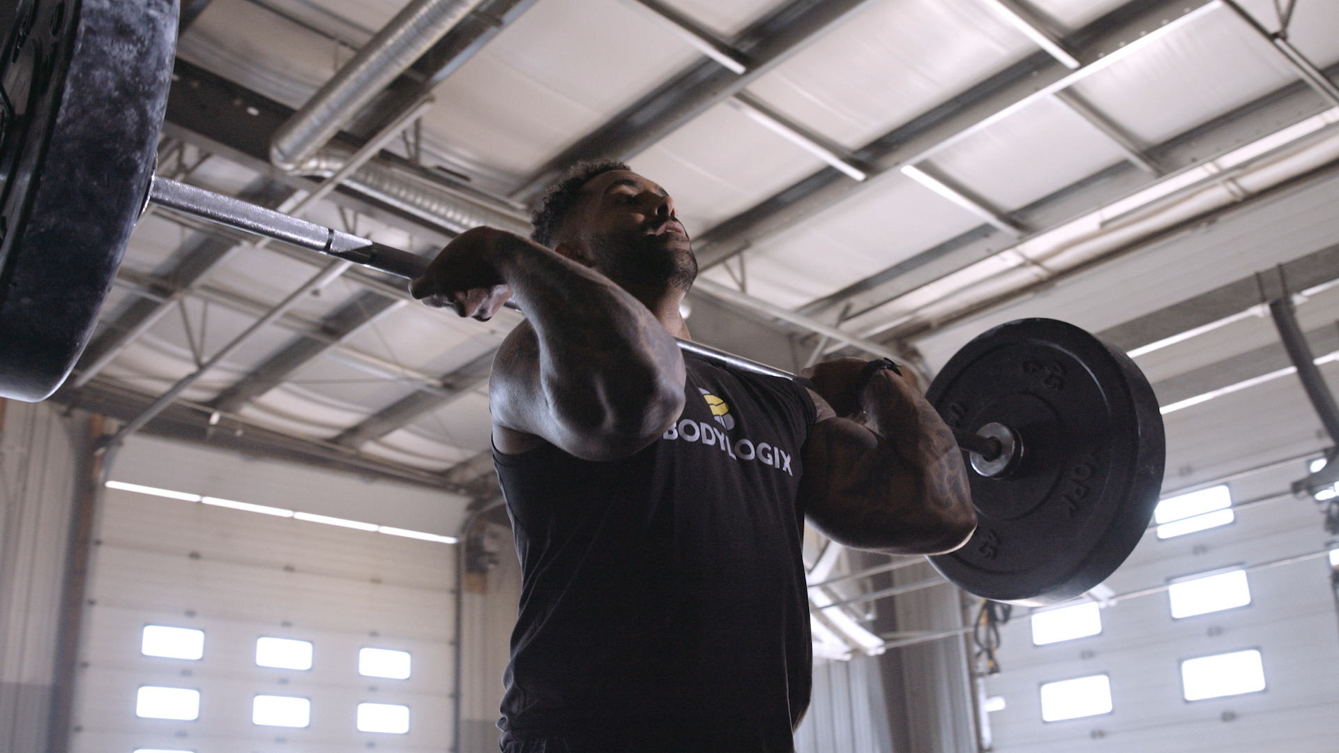 An image of a man lifting a barbell above his shoulders in a garage-like gym.
