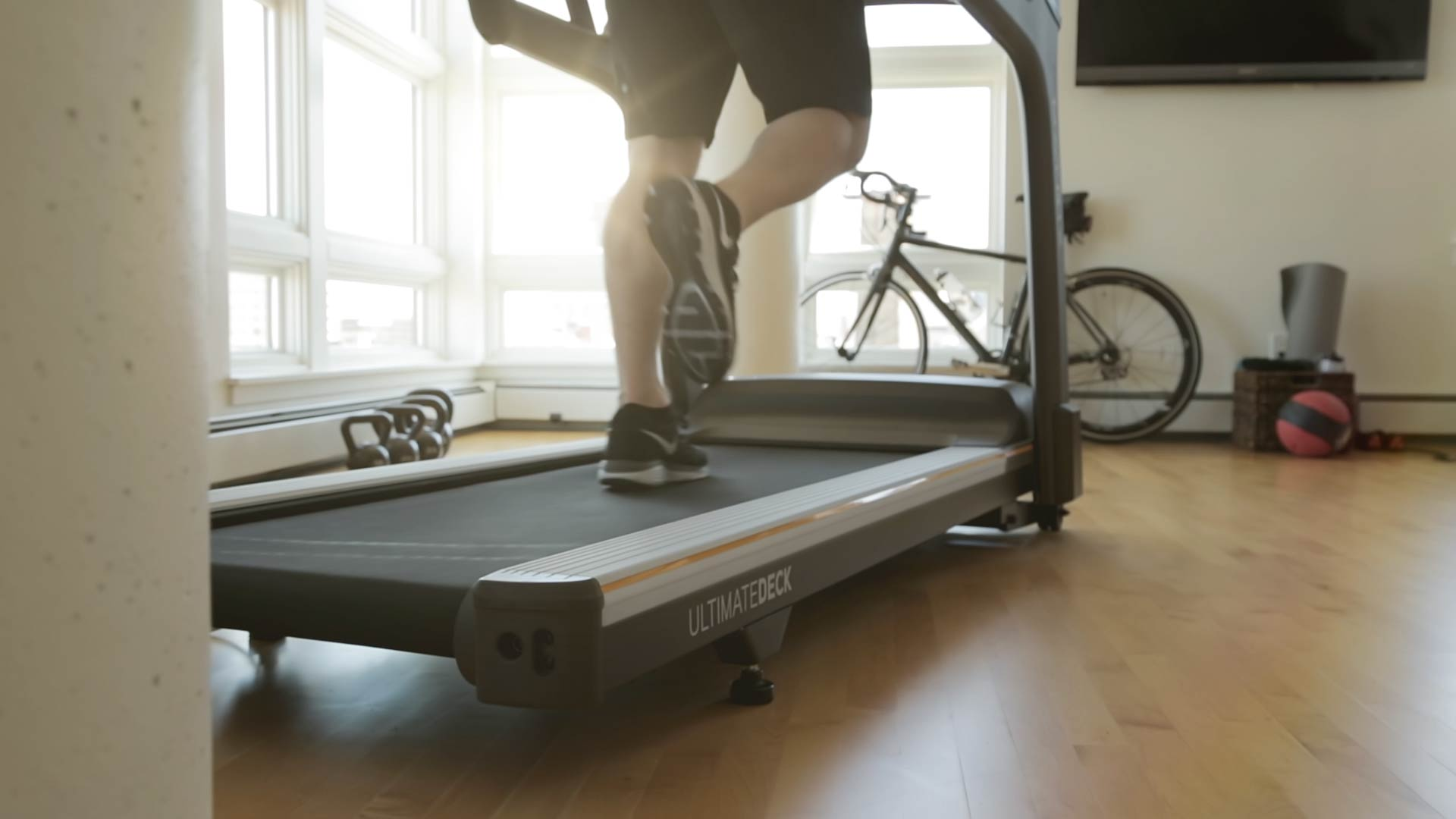 A cropped image of a man's legs running on a treadmill.