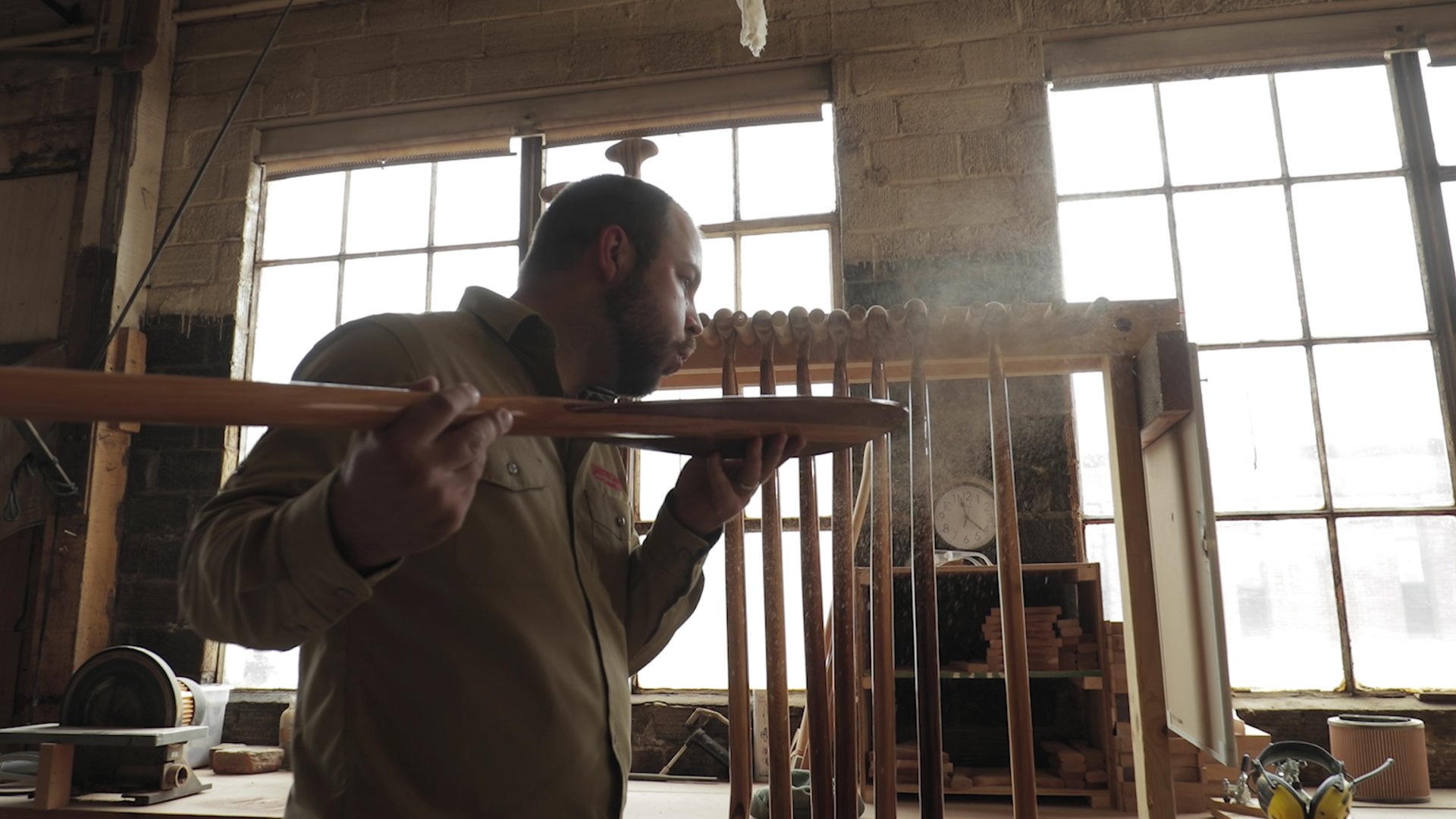 An image of a man blowing sawdust off of a canoe paddle his is crafting in a workshop.