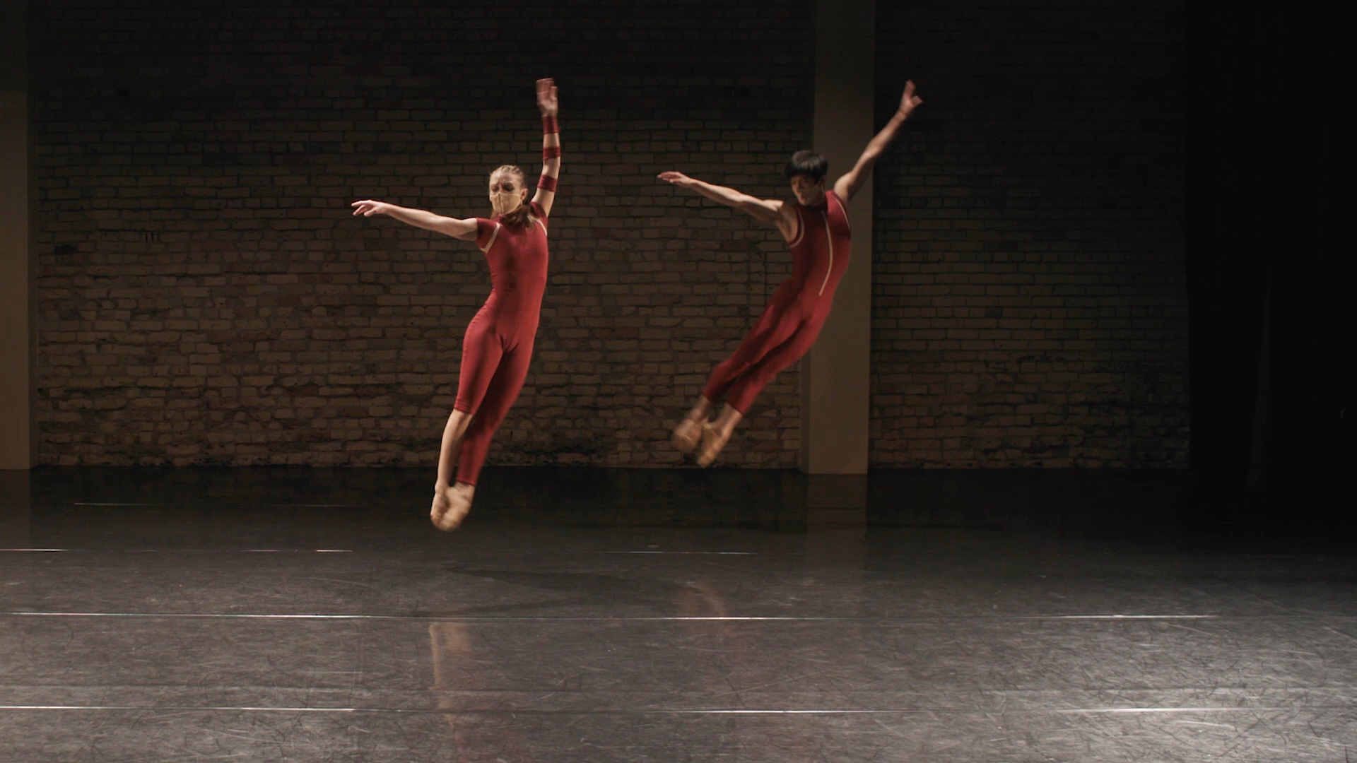 An image of two dancers in red leotards. Both of them are mid leap, with their legs together and arms in the air. They are in a dance studio, with a brick wall behind them.