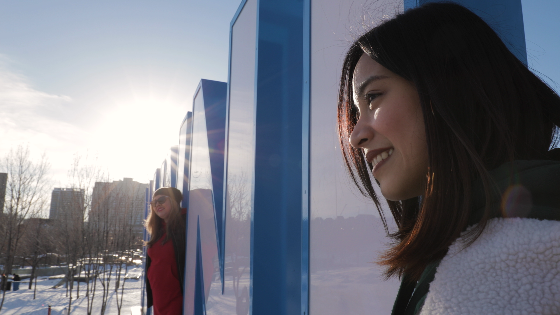 A profile image of a smiling woman standing beside the giant Winnipeg sign at the Forks in Winnipeg, Manitoba. The sun is shining and there is snow on the ground.